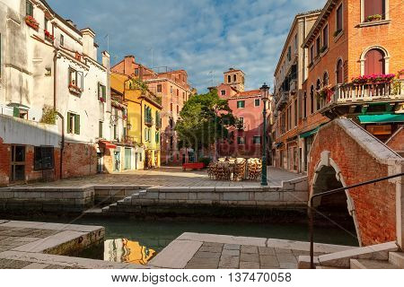 Colorful narrow lateral canal, square and pedestrian bridge in Venice, Italy