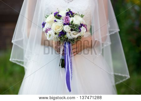 Young beautiful Bride holding bouquet of purple, violet, yellow, and cream-colored roses, and other flowers mixed with wild greens