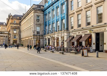 GLASGOW, SCOTLAND - JULY 05, 2016: Royal Exchange Square in Glasgow with people sitting outside a restaurant in summer.