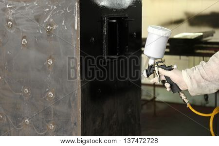 Worker painting metal construction with spray gun