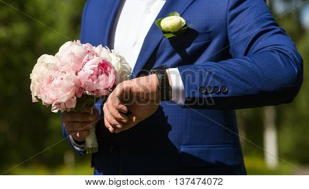 elegant stylish groom with bouquet of peonies waiting his bride and looks at watch.