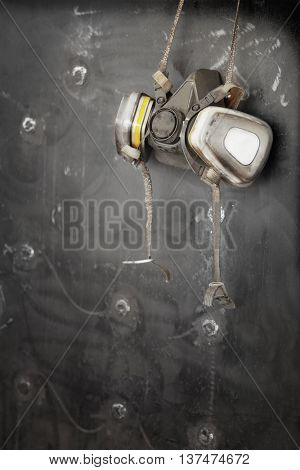 Respirator hanging on metal surface