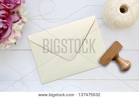 Mockup of ivory envelope with a rubber stamp next to it. Modern trend template for advertising. Delicate wooden background with flowers.