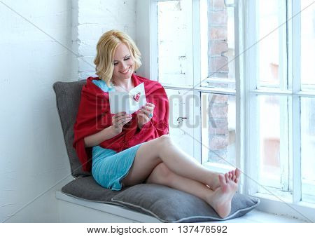 Happy Young Woman Sitting On Windowsill With Love Postcard In Her Hands.