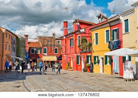 VENICE, ITALY - 17 OCTOBER 2015: Group of tourists sightseeing in Burano, Venice, Italy photographing the famous colorful fishing houses and shopping in the quaint shops and stores