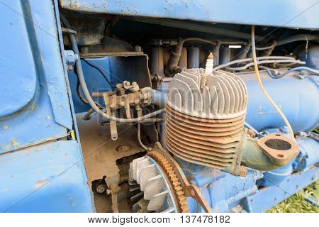 Old disused tractor engine painted blue with missing components