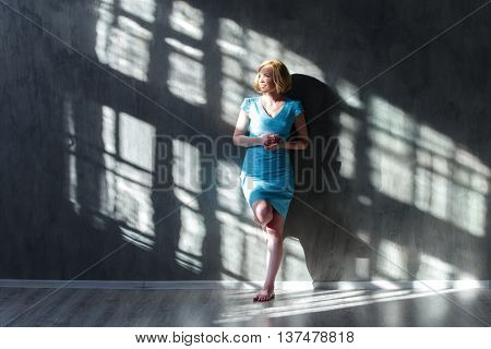 Attractive Blond Woman Leaning On The Wall And Squinting