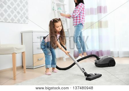 Daughter and mother using vacuum cleaner in room