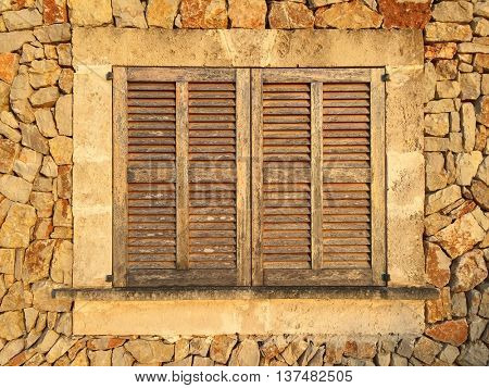 Stone wall and window with closed wooden shutters