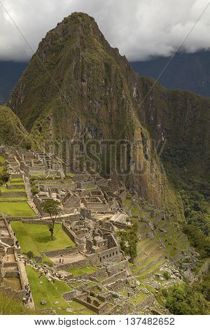 MACHU PICCHU CUSCO PERU - NOVEMBER 25 2011: People Visiting Lost Incan City of Machu Picchu near Cusco in Peru. Peruvian Historical Sanctuary and UNESCO World Heritage Site.