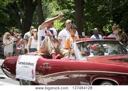 NEW YORK - JUNE 12 2016: Carmelo Anthony, professional basketball player for the New York Knicks rides in a car at the 59th annual National Puerto Rican Day Parade on 5th Avenue in NYC, June 12 2016.