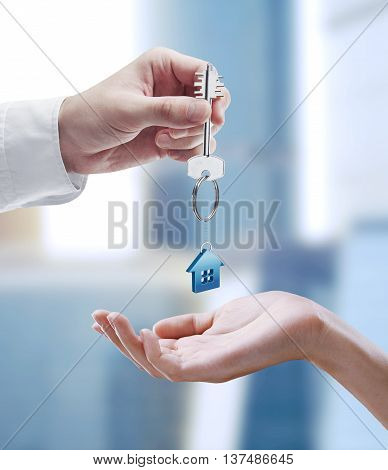 Man is handing a house key to a woman. Key with a keychain in the shape of the house.