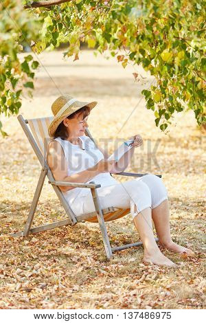 Senior woman sitting on a deck chair relaxing and reading