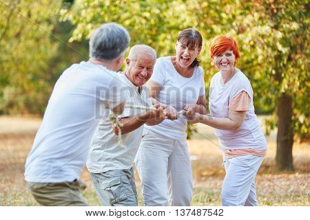 Group of senior citizens playing tug of war in summer in the park