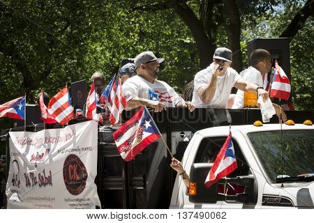 NEW YORK - JUNE 12 2016: DJs and entertainers wave flags and celebrate atop a float during the 59th annual National Puerto Rican Day Parade on 5th Avenue in New York City on June 12 2016.