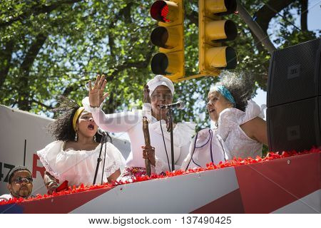 NEW YORK - JUNE 12 2016: Three female singers perform from on top of a float during the 59th annual National Puerto Rican Day Parade on 5th Avenue in New York City on June 12 2016.