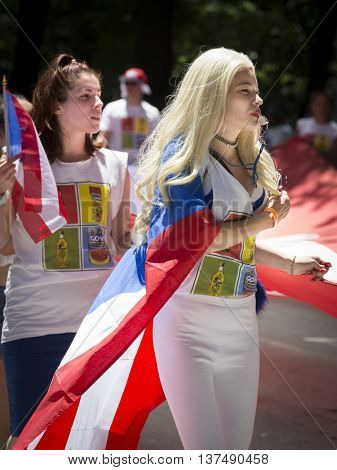 NEW YORK - JUNE 12 2016: A young woman holds the edge of a large flag as the group marches in the 59th annual National Puerto Rican Day Parade on 5th Avenue in New York City on June 12 2016.