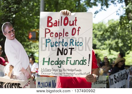 NEW YORK - JUNE 12 2016: A marcher displays the political message Bail Out People of Puerto Rico Not Hedge Funds in the 59th National Puerto Rican Day Parade on 5th Ave in New York City June 12 2016.
