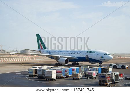 ABU DHABI, UAE - MARCH 27, 2015: Towing Aircraft Airbus A330 - MSN 1123 (EI-EJG) of Alitalia after landing at the airport in Abu Dhabi