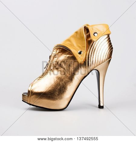 stylish gold female shoes over white background