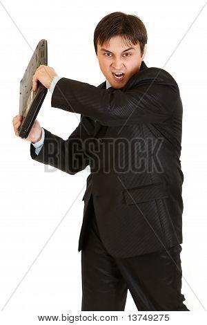 Stressed modern businessman brandishing laptop isolated on white
