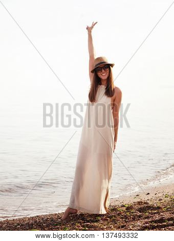 Joyful casual girl walking on a sea beach and happy smiling with hand up showing victory sign