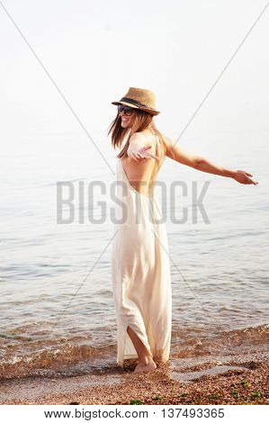 Young smiling woman enjoy summer holidays on a sea beach, long white dress with open back and hat