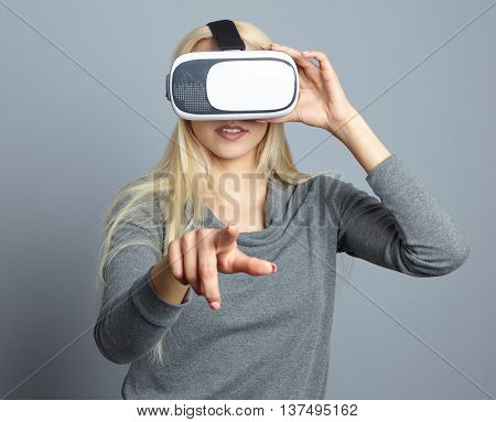woman using the virtual reality headset and one finger touch on air, focus on finger