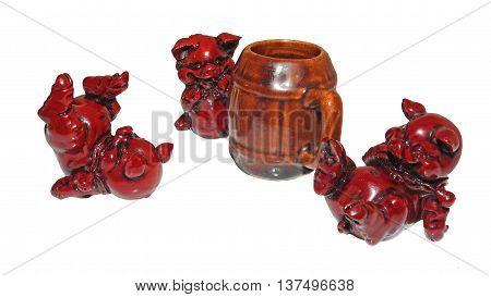 Three ceramic drunken pigs on white background.