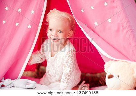 Smiling kid girl 3-4 year old sitting in tent outdoors