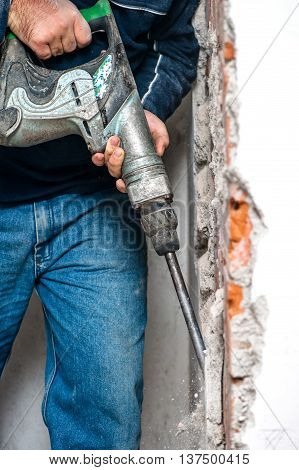 Professional Worker Handling An Jackhammer And Drilling Into Int