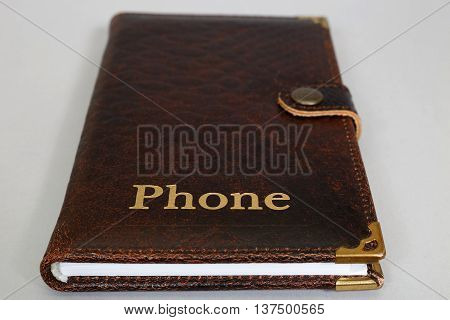 Brown notebook bound in leather with the words