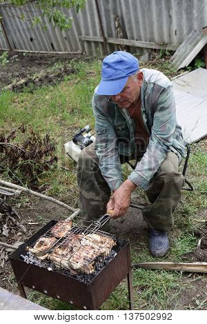 Senior man cooking catfish on a barbecue grill