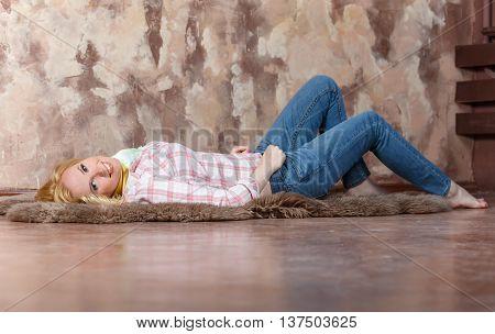 Pleased Blond Girl Lying On A Fur On The Floor