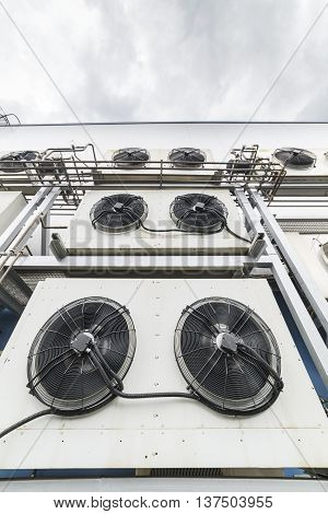 Industrial air conditioning units. A plurality of cooling units installed in the wall of a building.