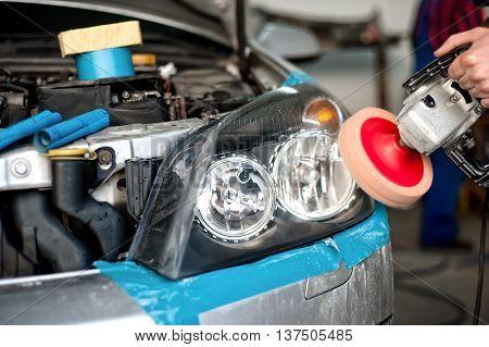 Auto Mechanic Working On Polishing A Car Headlight With Power Bu