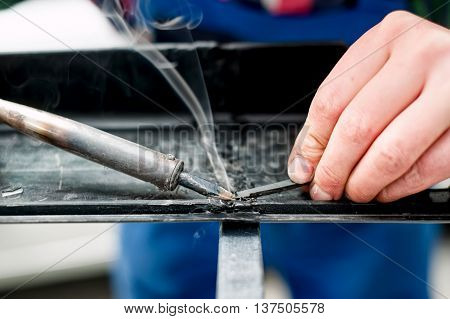 Professional Mechanic Using A Plastic And Synthetic Welder On Bo