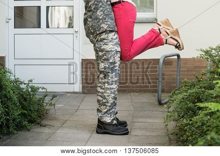 Low Section View Of Wife Embracing Her Husband In Army Uniform