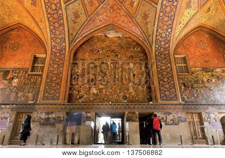 ISFAHAN, IRAN - OCT 17, 2014: Tourists inside the historical rooms with old murals and decoration of palace Chehel Sotoun on October 17, 2014. Safavid era Forty Columns palace was built in 1647 in Esfahan