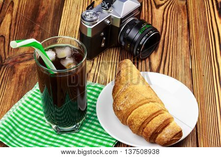Glassful of black coffee with ice and tubule on green napkin. croissant vintage camera wooden table in cafe. travel concept