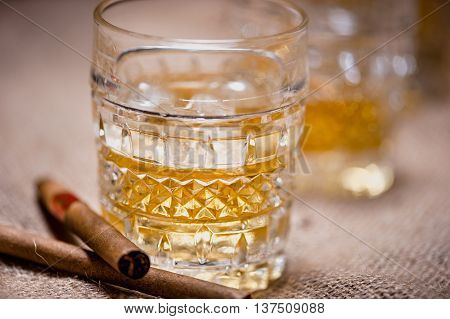 Close-up of whiskey glass on the rocks with cigars and vintage background