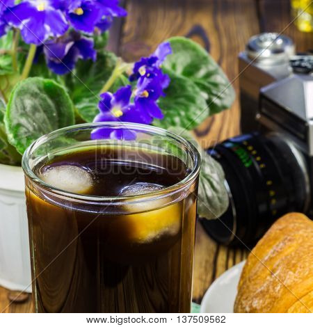 Glassful of black coffee with ice croissant vintage camera flowerpot on wooden table selective focus.