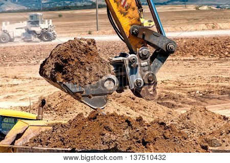Close-up Of Heavy Duty Excavator Scooping Into Earth And Loading