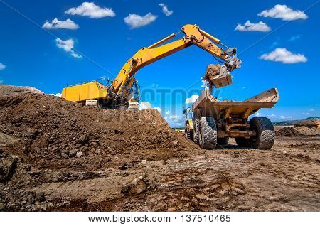 Industrial Excavator Loading Soil From Sandpit Into A Dumper Tru
