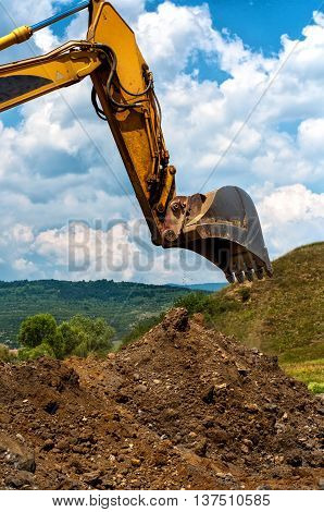 Loader Excavator Standing In Sandpit With Risen Bucket Over Clou