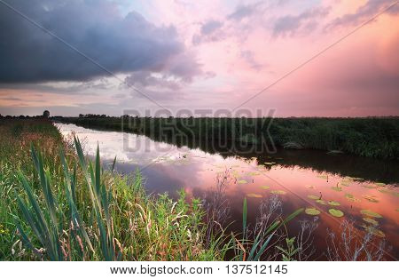 purple rainy sunset over river in summer
