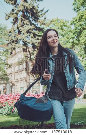 Summer sunny lifestyle portrait of happy young stylish woman tourist dressed in casual jeans denim clothes blue backpack on her hand. Smiling female walking in flowering park near famous Nevsky prospect in Saint-Petersburg Russia. Travel concept in Europe