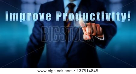 Industrial Manager is pushing the phrase Improve Productivity! on a touch screen. Business objective concept motivational metaphor call to a action and management challenge. Close up shot.