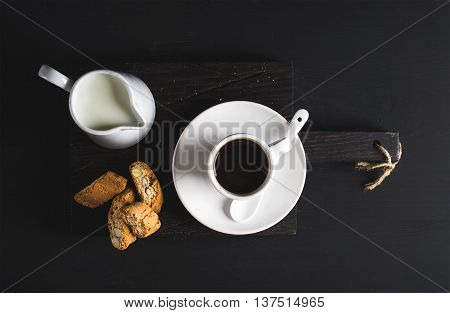 Cup of hot espresso, creamer with milk and cookies on dark rustic wooden board over black background, top view, horizontal composition