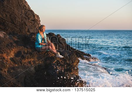Young blond woman tourist in blue shirt and jeans shorts sittig on rocks by the sea at sunset with bottle of lemonade, looking at sun and smiling. Kleopatra beach, Alanya, Mediterranean region, Turkey.